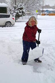 Woman shoveling winter snow off of a sidewalk in Boise, Idaho, USA.