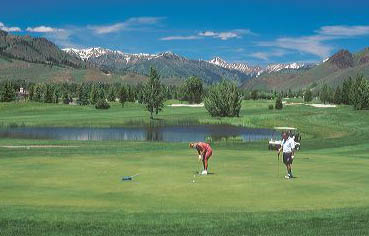 A couple golfing in Sun Valley, Idaho. golf, green, putt, mountains, idaho, scenic, course, cart, resort, vacation, holiday, destination, travel, tourism, recreation, exercise, sport, diversion, fun, romance
