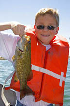 A twelve year old boy wearing a life jacket and holding a bass he caught while fishing in Idaho. MR