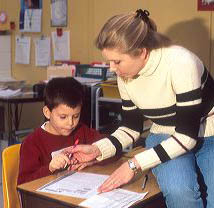 Elementary school teacher helping a student in her classroom. MR boy, student, elementary, classroom, education, study, school, curriculum, learning, teaching, teacher