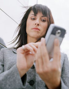 Business woman standing outside in front of office building, using mobile phone --- Image by © Royalty-Free/Corbis