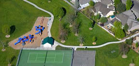 Aerial view of a park with playground equipment, tennis courts and a basketball court in Boise, Idaho.