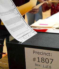 Voted ballot being put into a ballot box in Boise, Idaho, USA.
